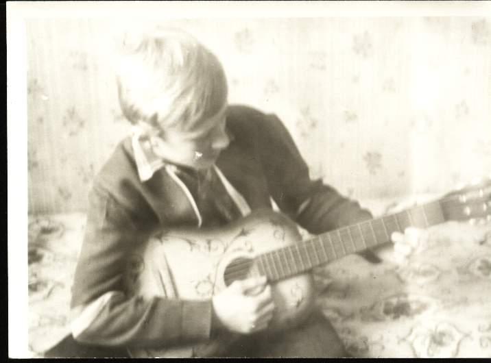 """1986 год, зима.  Первые ноты на гитаре.  Саша играет  """"В траве сидел кузнечик."""